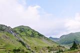 Photo of green capra peak, a small river and a road in fagaras mountains, Romania.