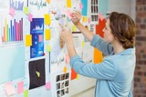 Businesswoman putting sticky notes on whiteboard - 117455692