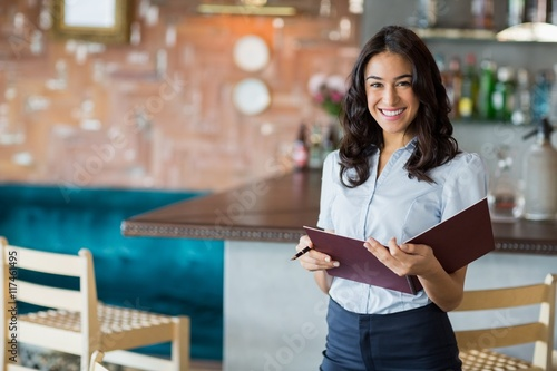 Smiling waitress holding a file