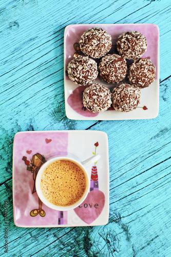 Fototapeta Cup of coffee and chocolate candy on a blue background
