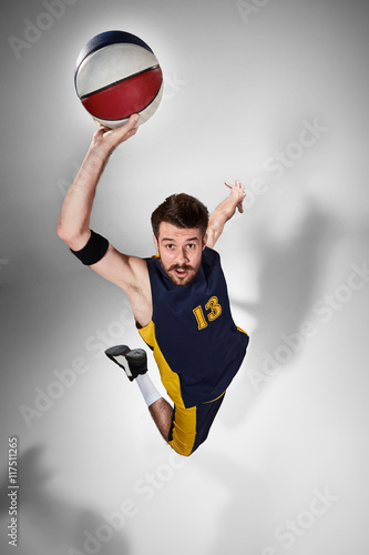 Fototapeta Full length portrait of a basketball player with ball