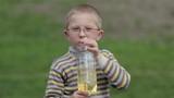 kid in glasses drinking water/child in glasses opens the bottle and drinking sugar water