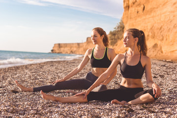 Two girls are doing pilates on the beach