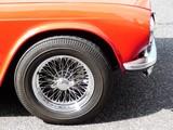 Chromspeichenrad mit Schnellverschluss eines roten englischen Roadster der Siebziger Jahre