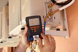 Instalador verificando el compresor de aire acondicionado