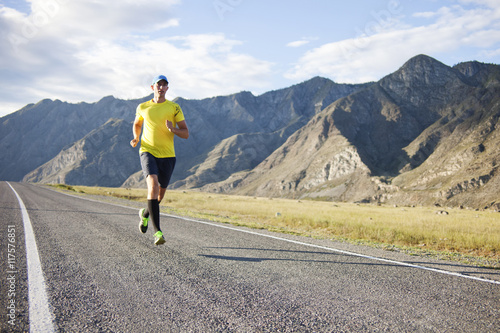 Young man running on mountain road