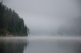 Mysterious landscape with fog, lake and forest