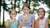 Three kids eat ice cream in waffle cone in the park.