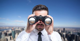 Businessman using binoculars to look at the city - 117670015