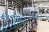 Water factory - Water bottling line for processing and bottling pure spring water into small bottles. Selective focus. - 117673258
