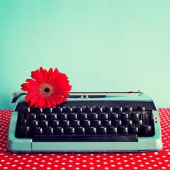 Vintage typewriter and red flower