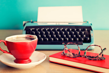 Turquoise typewriter, coffee cup and eyeglasses over red notebook