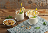 yoghurt in cups with a straw with muesli and banana