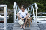 young man with dog on the pier