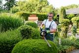 Gärtner bei Gartenarbeit - 117706822