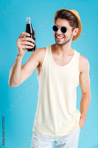 Poster Smiling man in hat and sunglasses holding bottle of soda