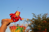 Textile handmade homemade toy fabric doll red spotted ladybug in a hand on a background of blue sky