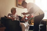 Nurse measuring blood pressure of senior patient in retirement h