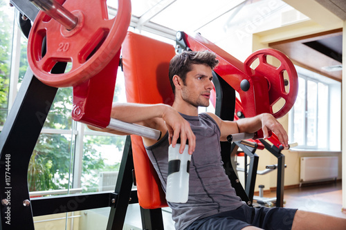 Portrait of a fitness man resting on bench at gym Poster