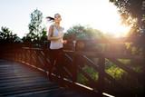Beautiful jogger crossing bridge - 117751485