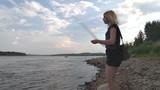 Girl Catches Fish with Bait. Girl skewer the bait on the hook and throws the bait into the river. Blonde catches a fish