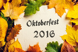 Oktoberfest sign and colorful autumn leaves. Paper background.
