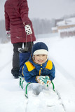 Mom pulls a sled with his son on snowy road