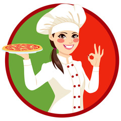 Young female Italian chef holding pizza and making ok sign with Italy flag on background