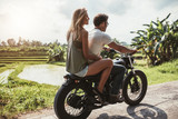 Man riding motorcycle with a woman on rural road