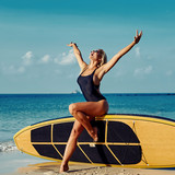 Beautiful fit blonde woman posing with surfboard near the ocean