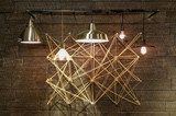 Modern light fixtures hanging in front of complex geometrical design. Abstract Interior design modern and minimal. Light bulbs displaying brightly.