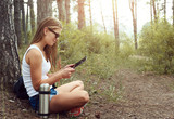 Young female traveler using digital tablet pc outdoors. Woman hiker resting in the forest with computer.