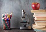 Microscope, pencils, books and apple