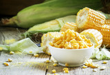 Canned sweet corn in white bowl, fresh cobs, wood background, se