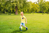 Sporting boy plays football in sunny park
