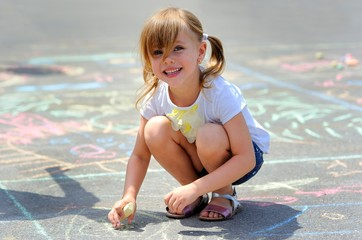 little girl draws a chalk