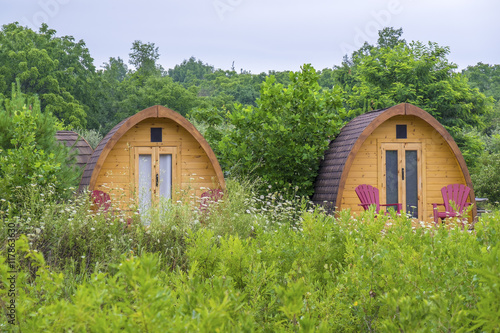Little Wooden Huts For Overnight Stay in a Summer Camping Ground Poster