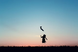 Silhouette of a beautiful girl jumping over sunset