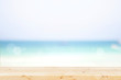 Quadro Wooden table with defocused blue sea, white sand beach background.