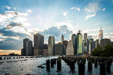 Panorama of Lower Manhattan and some pylons that stick out of the water on a cloudy day, in New York, USA