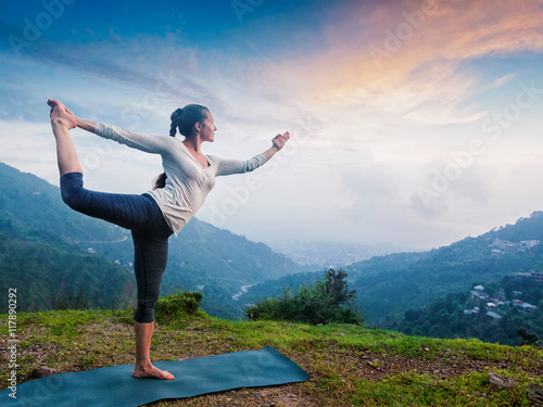 Woman doing yoga asana Natarajasana outdoors at waterfall - 117890292