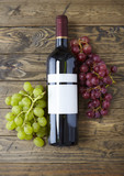 A bottle of red wine with bunches of grapes, arranged on a reclaimed wooden table top background