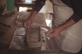 Male potter designing clay