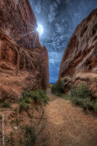 A narrow path through some Red Sandstone Rock, with the sun trying to burn through building storm clouds.
