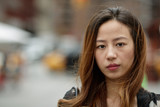 Young Asian woman in city serious face portrait - 117916019