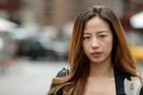 Young Asian woman in city serious face portrait - 117916024