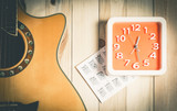 Music Practice time concept with acoustic guitar and orange wall clock