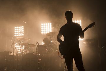La silhouette d'un guitariste durant un concert