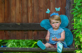The sad little fairy in a blue dress with of white daisies.