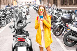 Young woman in yellow sweater using mobile phone on the street full of scooters in Italy.